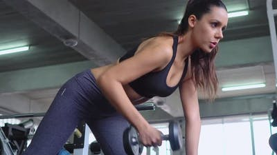 Woman lifting dumbbell in a fitness