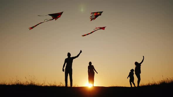 Active Family with Children Launches Kites in a Picturesque Place at Sunset