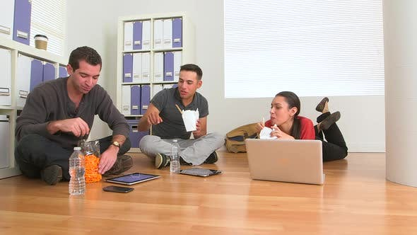 Thumbnail for Multi ethnic group of office workers eating food on floor