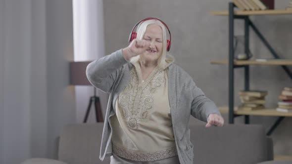 Relaxed Positive Retiree in Headphones Dancing to Music in Headphones Smiling