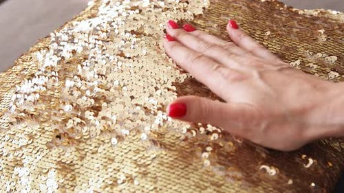 Gold sequins pillow. Touches a shiny textured surface.