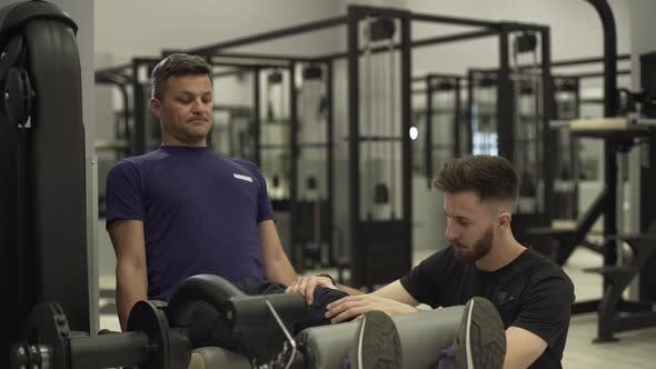 Thumbnail for Handsome Adult Man Is Engaged in the Gym with an Individual Trainer in the Gym