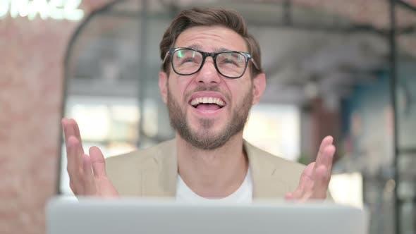 Man with Laptop Feeling Shocked