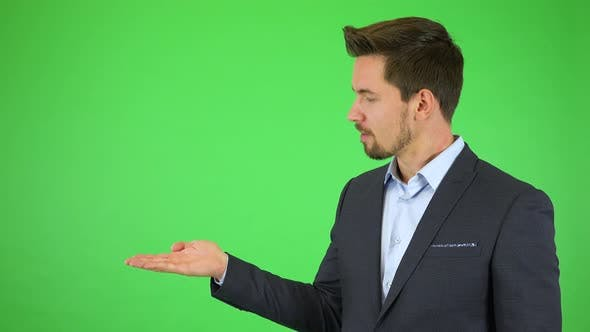 Thumbnail for A Young Businessman Talks To the Camera, Puts Out a Hand with a Product and Continues Talking