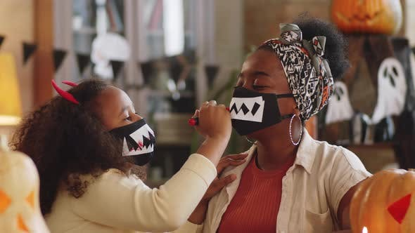 Black Girl and Mom Drawing Blood on Vampire Teeth on Halloween Mask