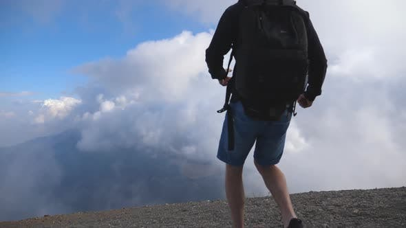 Thumbnail for Young Male Hiker with Backpack Reaching Up Top of Mountain with Cloudy Sky at Background and Raising