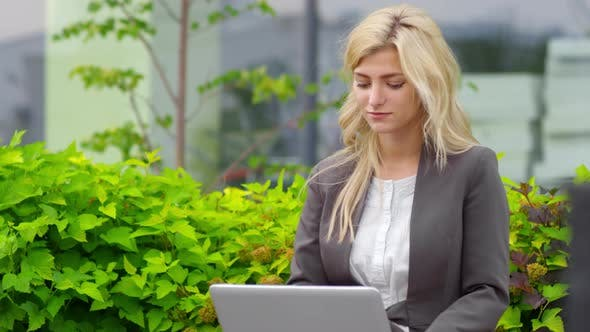 Thumbnail for Blonde Businesswoman Working Remotely in Park