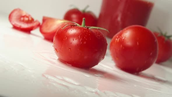 Thumbnail for Two Ripe Tomatoes Fall On A Table, Splashing Drops. Fresh Tomato Juice On A Background