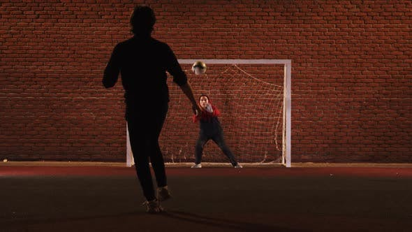 Cover Image for Two Young Friends Playing Football on the Outdoor Playground at Night - Protecting the Gates