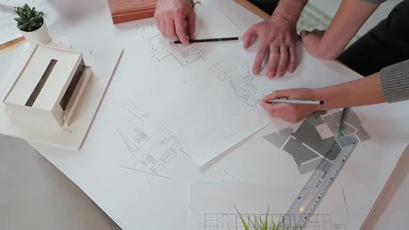 Thumbnail for Close Up Hands of Two Workers Discussing Building Drawings in Office, Closeup Shooting of Arms
