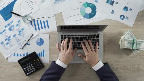 Office Employee Working on Laptop at Desk, Company Revenue Analysis, Bills Aside