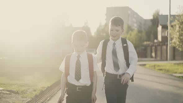 CU, Tracking, Slow Motion: Two Schoolchildren Go Home After School, They Talk, Smile