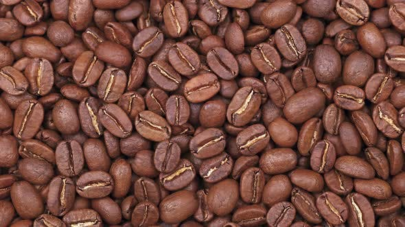 Sliding roasted Arabica coffee beans background