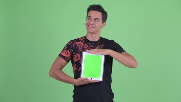 Cover Image for Happy Young Handsome Man Thinking While Showing Digital Tablet