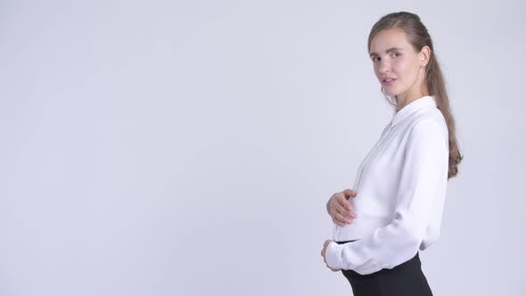 Thumbnail for Profile View of Young Happy Pregnant Businesswoman Looking at Camera