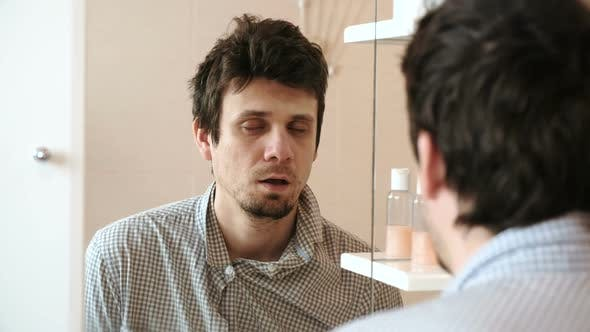 Thumbnail for Tired Man Who Has Just Woken Up Looks at His Reflection in the Mirror Almost Asleep Standing Up