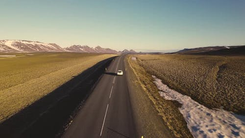 Beautiful Aerial Shot of Road in Between Open Fields With Sun Gleaming Bright