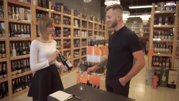 Thumbnail for Pretty Short-haired Girl Seller Offers Wine To the Visitor. Male Customer Takes a Bottle of Wine