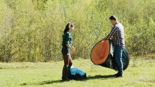 Beautiful Young Couple Setting Up the Tent for Campsite