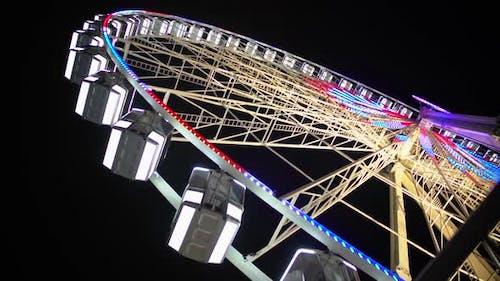 Giant Wheel Starts Rotating and Gaining Speed, Bright Illumination Sparkling