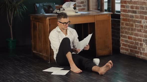 Thumbnail for Man liest Seiten auf dem Boden