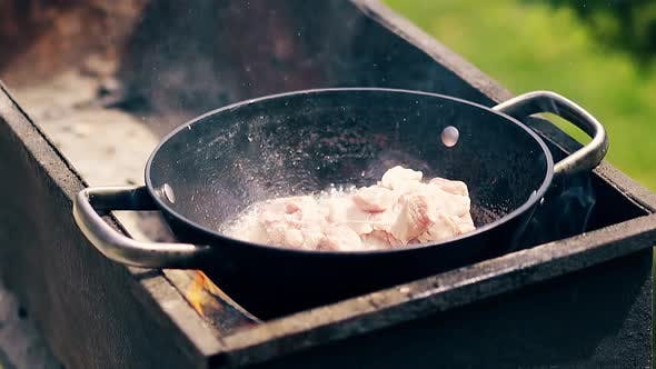 Thumbnail for Close-up, Slow Motion: Pork Meat Is Fried in Saucepan on Charcoal. The Person Adds Meat To the