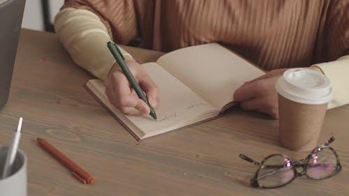 Person schreibt in Notizbuch von Schreibtisch