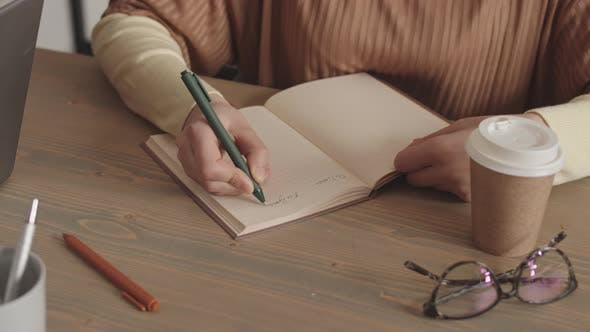 Person Writing in Notebook by Desk