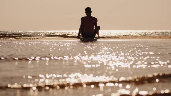 Thumbnail for Back View of Alone Young Man Sitting on a Small Sand Island