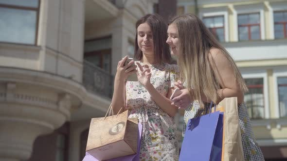 Thumbnail for Two Cute Girlfriends After Shopping with Shopping Bags Taking Selfie on Cellphone Outdoors