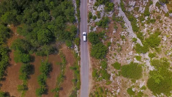Thumbnail for Aerial drone view of a minivan car vehicle driving on a rural road.