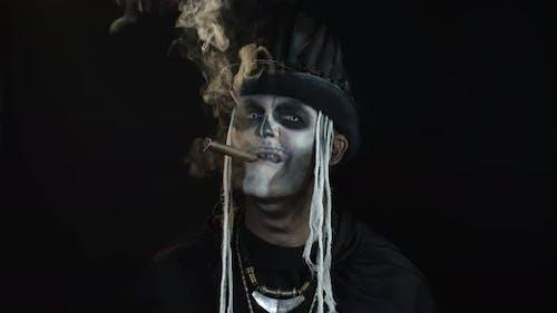 Frightening Man in Skeleton Halloween Cosplay Costume Smoking Cigar, Making Faces, Smiling