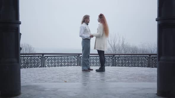 Thumbnail for Long Shot of Stylish Man in Retro Style Shirt and Vest Bending Down on One Knee and Proposing