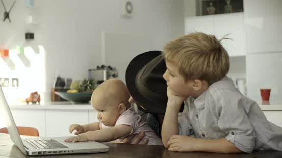 Father and children with laptop in kitchen
