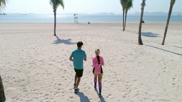 Drone view of couple starting up their jogging training. Shot with RED helium camera in 8K