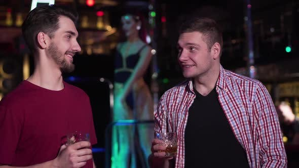 Thumbnail for Two Handsome Caucasian Men Talking and Drinking Alcohol in Night Club, Young Positive