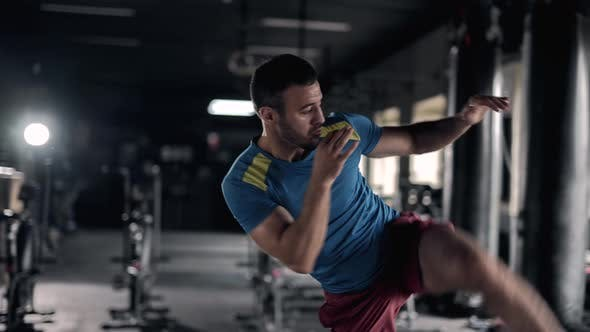 A Muscular Sportsman is Doing Exercises