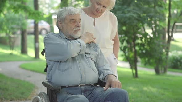 Thumbnail for Portrait of Frustrated Senior Man in Wheelchair Kissing Hand of Caring Old Woman. Depressed