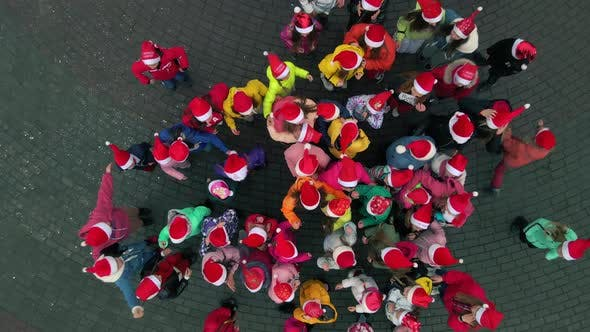 Many happy kids with Santa Christmas hats jumping on the square. Slow motion Top down aerial view.