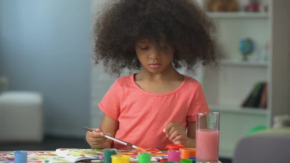 Thumbnail for Playful Afro-American female kid painting at workshop, leisure activity and art