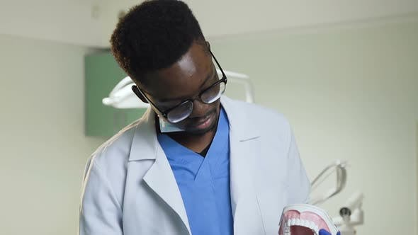 Thumbnail for African Male Dentist Showing How to Clean Teeth with Toothbrush on a Plastic Model