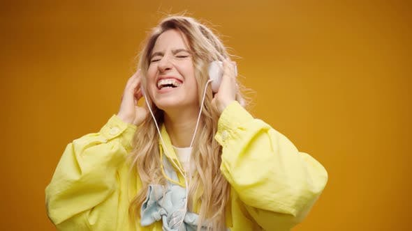 Young Woman Listening to Music with Headphones Against Yellow Background