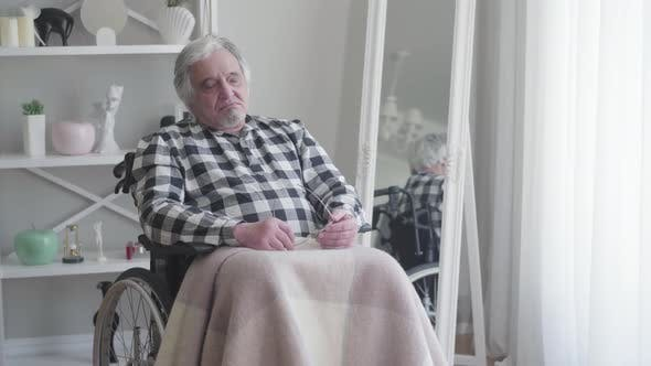 Thumbnail for Elderly Caucasian Grey-haired Man Sitting in Wheelchair and Signing. Old Male Retiree Suffering From