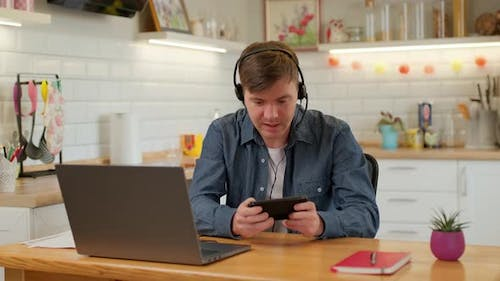 Happy man is playing video game at home using modern smartphone touching screen