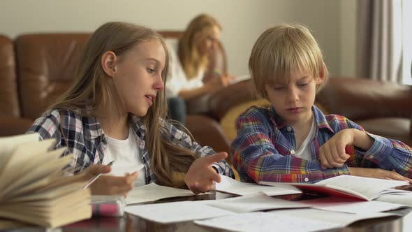Thumbnail for Adorable Little Brother and Sister Studying at Home in the Foreground While Their Mother Sitting