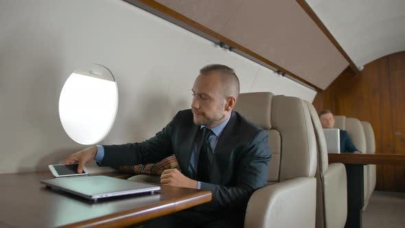 Confident Businessman in Formal Suit Travel on His Private Jet and Chat on Cell Phone