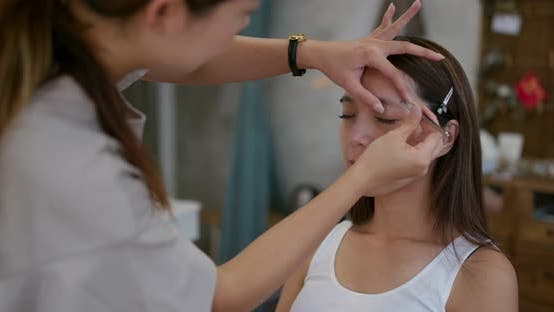 Thumbnail for Young woman having make up by artist in the studio
