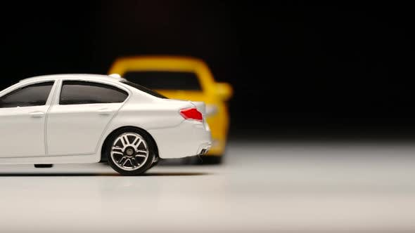 Thumbnail for Yellow toy car bumps into standed white toy car