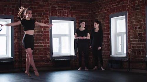 Gymnastique Blonde Jeune Femme montre des exercices de gymnastique dans le studio à d'autres femmes