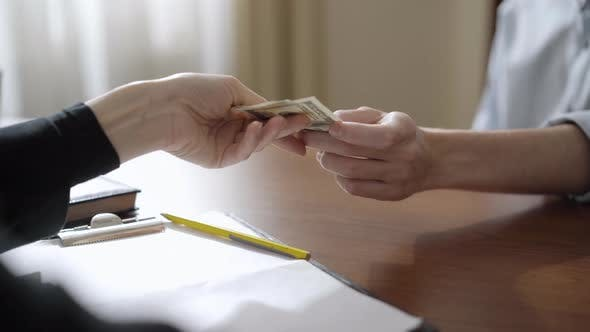 Unrecognizable Man and Woman Passing Money Over Table and Shaking Hands